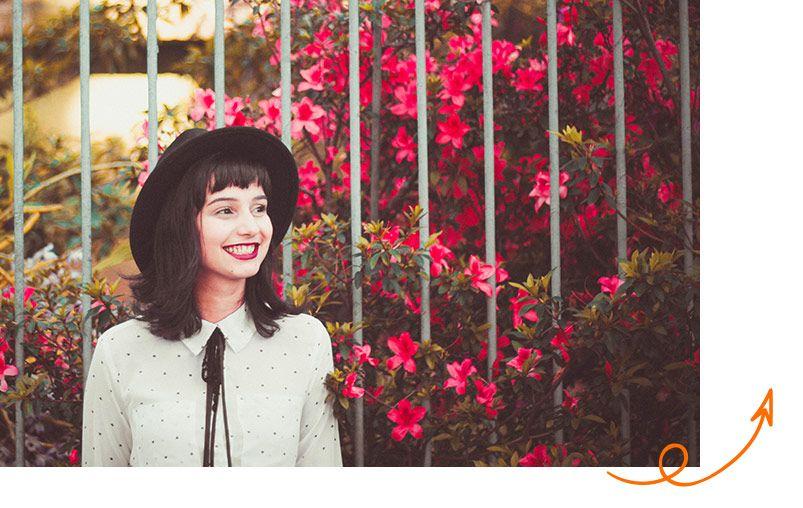 Chica paseando delante de unas flores