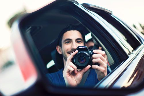 Un chico sacándose una foto en el espejo de un coche