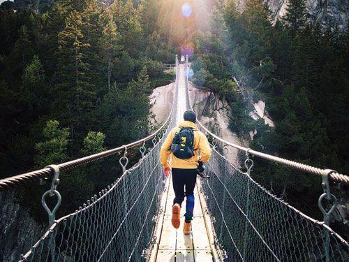 Un chico corriendo por un puente en la naturaleza