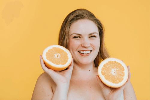 Chica sonriente sostiene una naranja