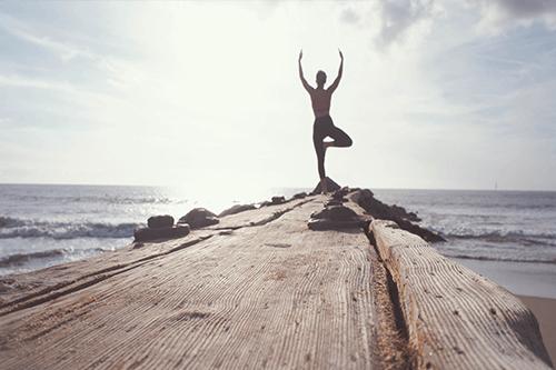 Una chica haciendo yoga en el muelle