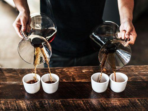 Manos-de-una-persona-sirviendo-cafe-en-tazas