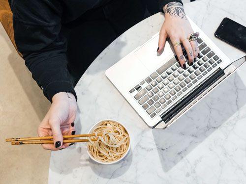 Persona-comiendo-mientras-mira-un-ordenador