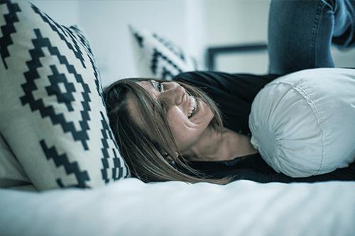 Mujer riéndose en cama
