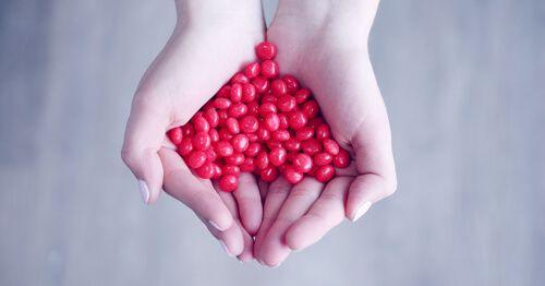 Dos-manos-de-mujer-sujetando-caramelos-rojos (1)