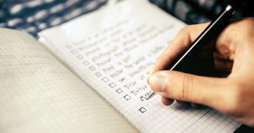 Mano-escribiendo-una-lista-en-un-cuaderno
