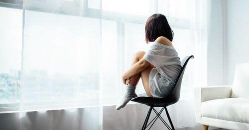 Mujer-sentada-sobre-una-silla-y-mirando-por-la-ventana