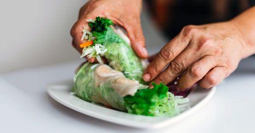 Como-evitar-los-atracones-por-ansiedad-comiendo-sano---Manos-masculinas-cogiendo-burritos-vegetales